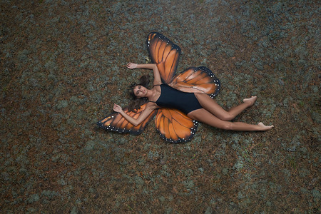 A girl in a butterfly suit lies on the ground
