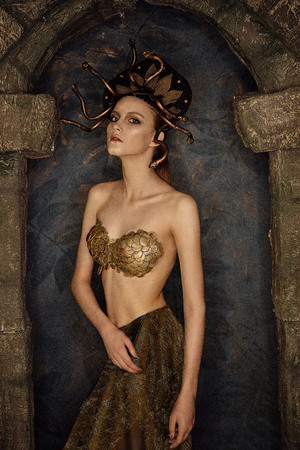 girl costume jellyfish gorgon with gold bra from scales in a stone arch