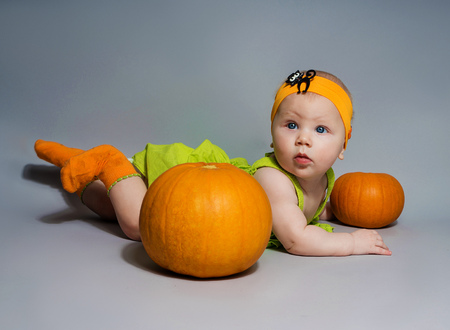 babe girl lies on stomach with two pumpkins on grey background