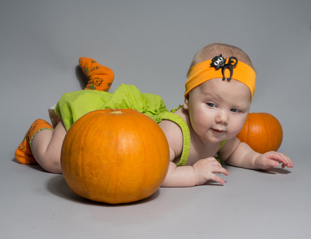 beautiful baby girl in a green dress with orange bow on her head lying on his stomach on a grey background including pumpkins