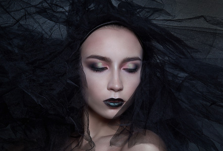 High Fashion Model Girl Portrait with Trendy gothic Black Make up, dark portrait. Halloween Vampire Woman with black matte lips over deep blue background. 写真素材