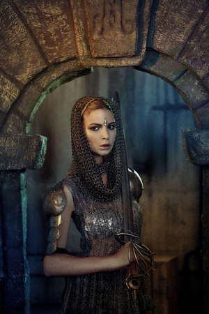 A beautiful warrior girl with a sword and in armor. A model in a chain skirt and a vest in a mysterious plase. Fantasy photo.