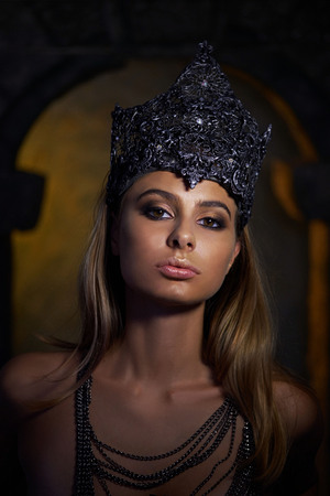 Portrait of a Gothic Princess. Beautiful young brunette woman in metal crown 写真素材