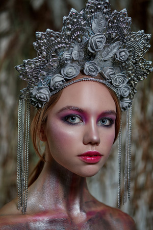 girl in silver makeup and red lips in silver headdress on nature background 写真素材 - 117282166