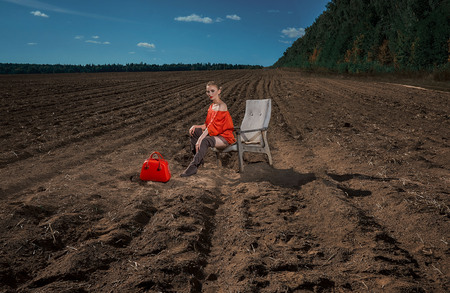 girl in a red dress with a red bag sits in a chair on the tillage field