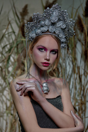 girl in silver makeup and red lips in silver headdress on nature background