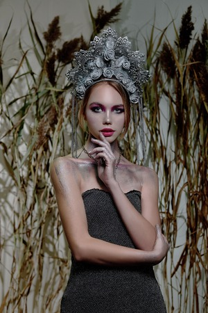 girl in silver makeup and red lips in silver headdress on nature background 写真素材 - 117282196