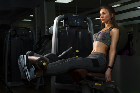 Beautiful girl athlete is engaged on the simulator in the gym on a black background