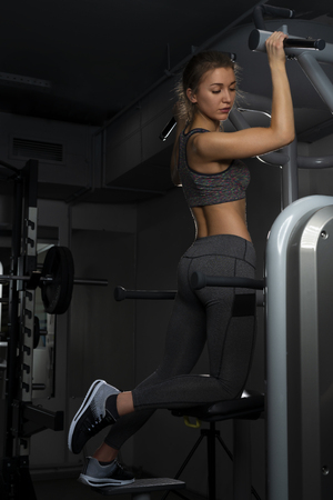 Beautiful sportamenka girl engaged on a simulator in the gym on a black background