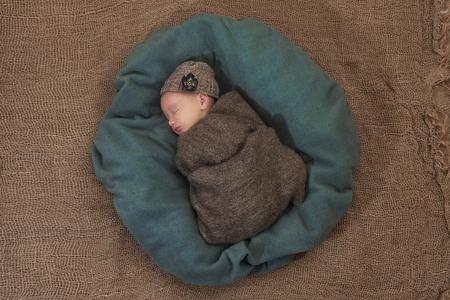 newborn girl sleeps on sackcloth, portrait, flowers, brown 写真素材 - 122719527