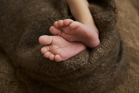 legs of a newborn girl are on sackcloth