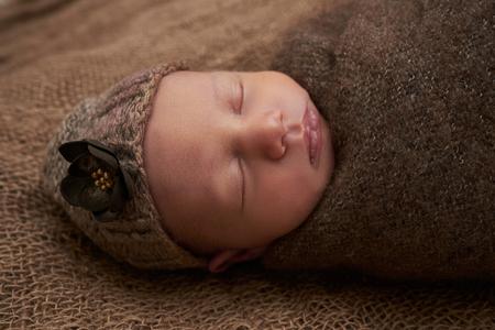 newborn girl sleeps on sackcloth, portrait, flowers, brown 写真素材 - 123044665