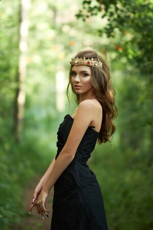 young, beautiful girl in a black dress with a crown in the forest 写真素材 - 128907340