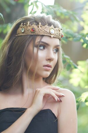 young, beautiful girl in a black dress with a crown in the forest 写真素材