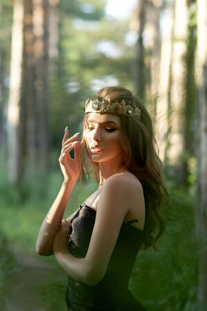 young, beautiful girl in a black dress with a crown in the forest Imagens - 128907341