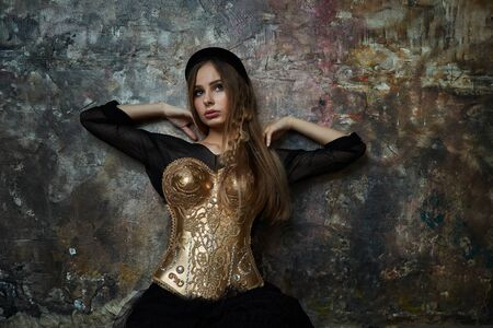 girl in a black dress and a gold corset against a blue wall