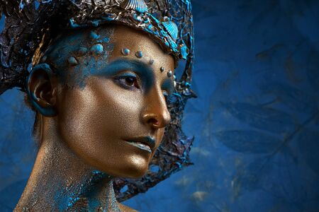 a girl in gold blue creative makeup and headdress