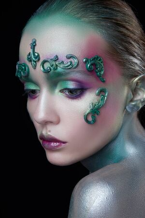 young beautiful girl with creative make-up of green and purple flowers Stok Fotoğraf - 129831771