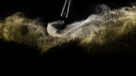 Cosmetic brush with gold cosmetic powder spreading for makeup artist and graphic design in black background, look like a luxury mood.