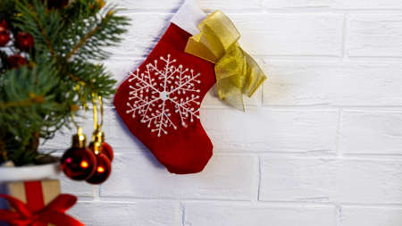 Selective focus Red and white Christmas stocking hanging from a clothesline against a white brick wall background. Christmas background. Christmas tree and red balls 写真素材
