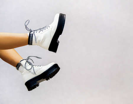 banner for a shoe store Girl's legs in white leather shoes from the new collection on a light background Girl's legs in fashionable eco-leather shoes Fall-Winter 2020........ Foto de archivo