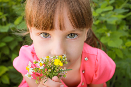 smells:  Girl smells the flowers Stock Photo