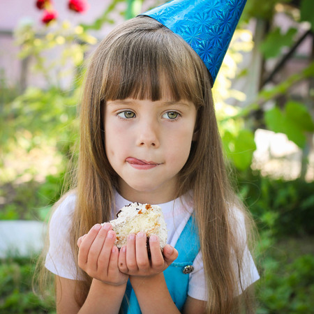 happy girl eats a cake on birthday party  photo