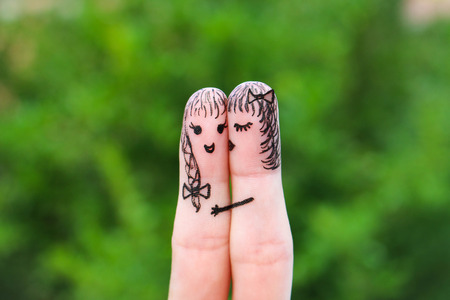beautiful lesbian: Face painted on the fingers. woman is kissing his girlfriend on the cheek
