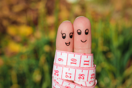 Finger art of a Happy couple with meter. The concept of losing weight together. photo