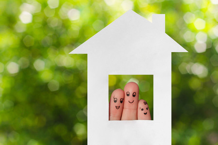 Finger art of a family. Family looking out of the window of the house out of paper.
