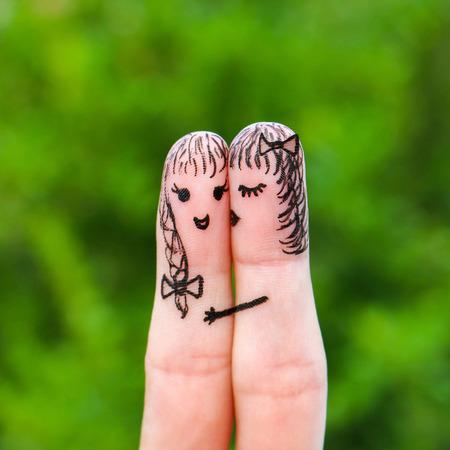 cheek: Finger art. woman is kissing his girlfriend on the cheek