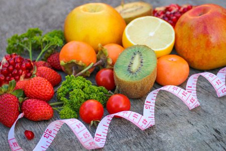 proper: Fruits, vegetables and in measure tape in diet on wooden background Stock Photo