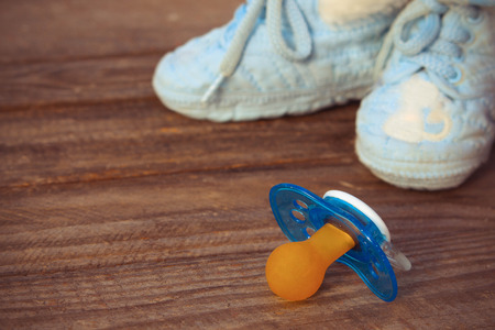 baby shoes and a pacifier on the old wooden background photo