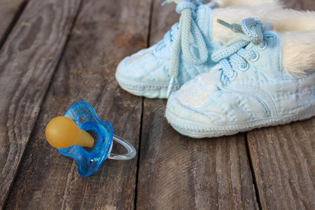 baby shoes and a pacifier on the old wooden background. photo