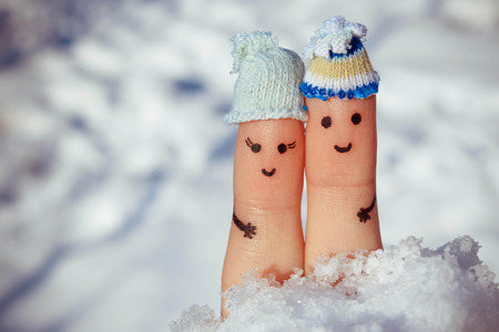 Finger art of a Happy couple on the background of snow. A man and a woman hug. Toned image. photo