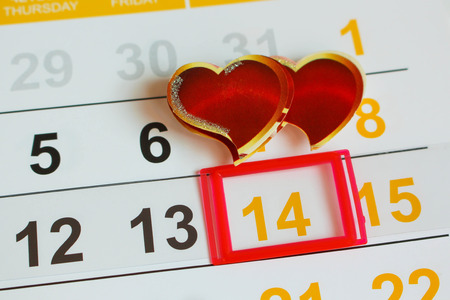 Date February 14 marked on the calendar. Two hearts the concept of love. photo