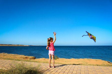 bluer: A little girl runs into the sky flying snake by the sea Stock Photo