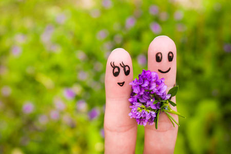 giving the finger: Finger art of a Happy couple. Man is giving flowers to a woman.