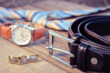 cufflinks: Leather belt, tie, cufflinks and watches on the old wood background. Toned image.
