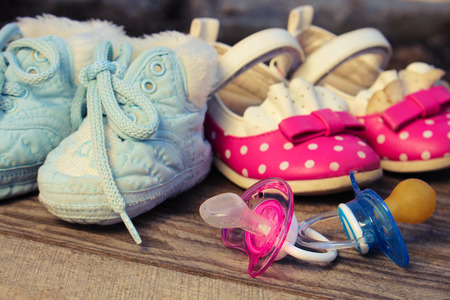 pacifier: Baby shoes and pacifiers pink and blue on the old wooden background. Toned image.