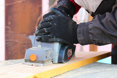 planer: Hands of the carpenter at work with an electric planer