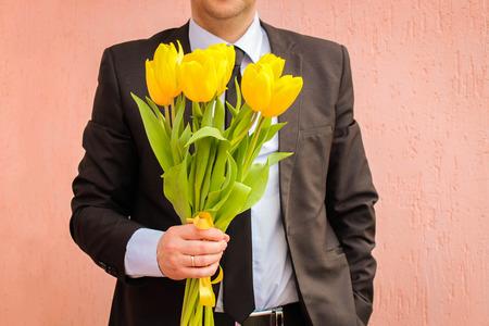 Een man, gekleed in pak, bedrijf boeket van gele tulpen. Stockfoto