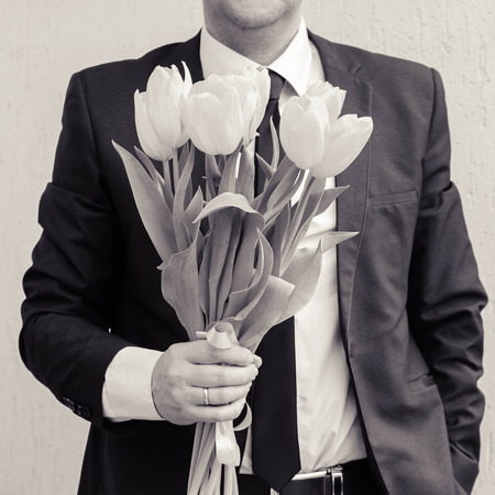 gives: A man wearing a business suit, holding a bouquet of tulips. The man gives a bouquet of flowers. Black and white shot. Stock Photo