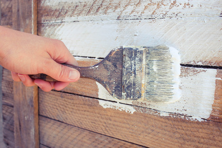 treated board: Female hand paint white paint boards old tassel Stock Photo