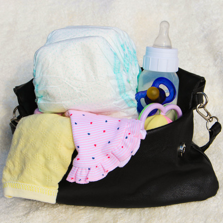 Womens handbag with items to care for the child