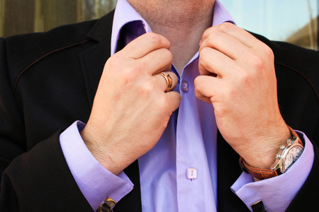primp: A man in a business suit straightens his shirt