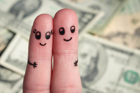 Finger art of a Happy couple. A man and a woman hug on the background of money.
