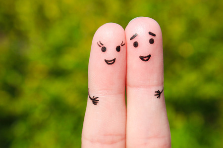 finger: Finger art of a Happy couple. A man and a woman hug on the background of green leaves