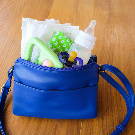 Women handbag with items to care for the child: bottle of milk disposable diapers rattle pacifier and baby clothes. Banco de Imagens