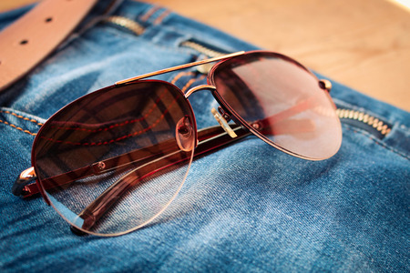 in jeans: Gafas de sol en fondo de pantalones vaqueros. Entonado imagen.